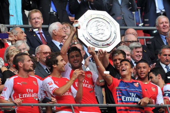 Arsenal's French striker Olivier Giroud (CL) and Arsenal's Chilean midfielder Alexis Sanchez (CR) raise the Community Shield trophy after Arsenal won the FA Community Shield football match between Arsenal and Manchester City at Wembley Stadium in north London on August 10, 2014.