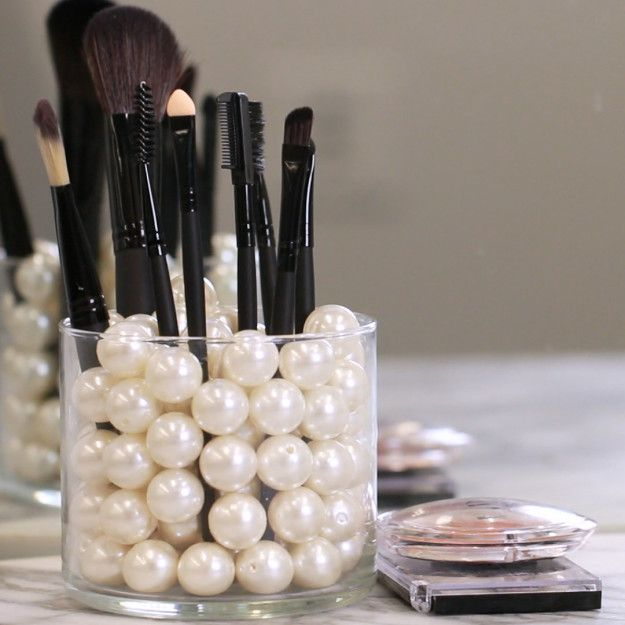 Fill the empty jars with pearls, beads, rice, or coffee beans for a decorative way to store your makeup brushes. | How To Make Clever Bathroom Organizers Out Of Old Candle