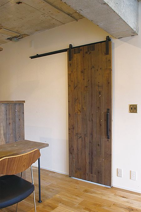 洗面所の引き戸をこんな風にできたら理想。アウトセットの引き戸/築42年の中古マンションをフルリノベーション。 キッチンカウンターやカップポード、ダイニングテーブルやベンチ、扉など、同じ材木で揃えて製作。 扉の滑車、取手、窓などに使用したアイアンが、経年の醸し出せる味わい深い空間を創出。