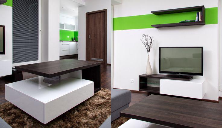 Konferenční stůl koncepčně navazuje na televizní stěnu a obsahuje jak otevřené, tak uzavřené úložné prostory v podobě výsuvů. Nábytek v obývacím pokoji je řešen bez úchytek. Pohodlné otevírání výsuvů zajištuje přesah čílka ve spodní části skříňky. Otevřená část televizní skříňky je navržena tak, aby se do ní mohlo pohodlně umístit příslušenství k televizi.