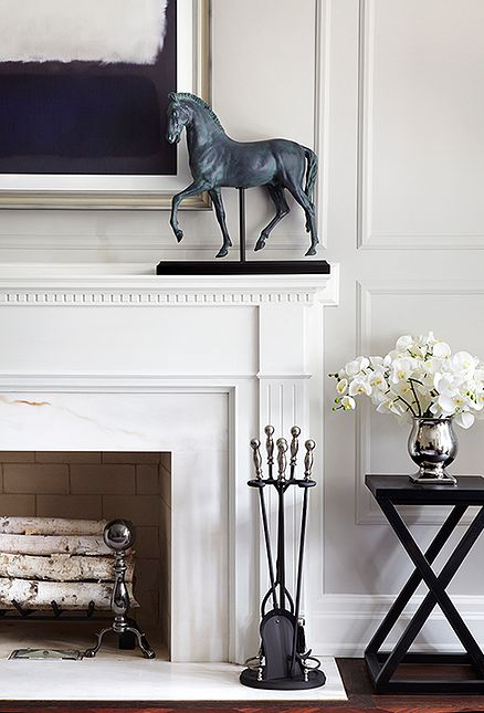 Cream classic family room element. Off-white mantel decorated with marble, birch logs, black mantel accessories, x-shaped side table, polished chrome vase full of white orchids, horse sculpture.