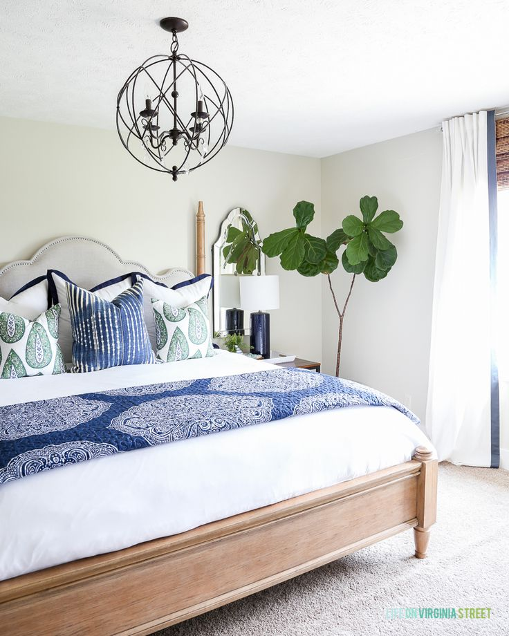 Gorgeous blue, white and neutral guest bedroom makeover using Dutch Boy Paints. Full step-by-step tutorial explains how to paint over striped walls without leaving any lines. New paint color is the brand's Platinum Plus Paint + Primer in Existence (420-1DB). Love the paisley bedding, iron orb chandelier and the fiddle leaf fig tree. #ad