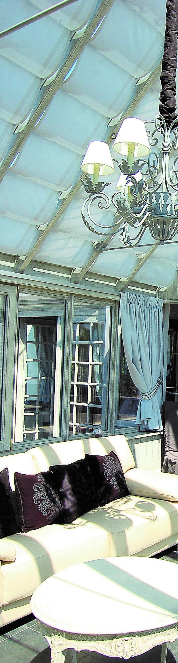 Des stores de toiture immaculés, des rideaux, un lustres éclairant en point central; des détails qui dans cette véranda font la différence.