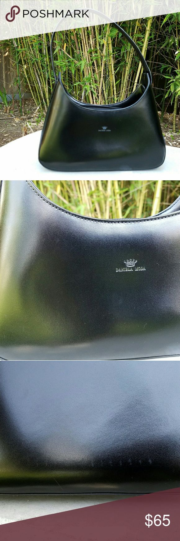 """Daniela Moda Italian Black Vera Pelle Handbag NWOT. High quality leather and craftsmanship on this free-standing purse. Very small marks in one area near bottom are hardly visible to naked eye-  but shows up mre in photograph (see 3rd photo). Very  sophsticated bag. 9"""" length, 4-1/2"""" bottom to zipper, 13-1/2 inches from bottom to top of strap. Daniela Moda Bags Mini Bags"""