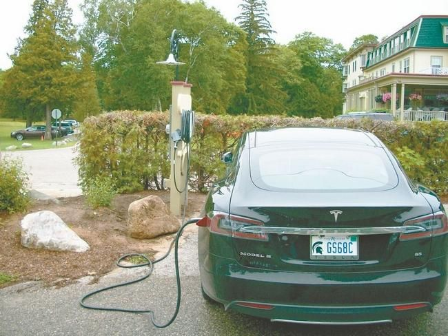 An electric car is receiving a battery charge at Stafford's Bay View Inn in Petoskey, which offers both a Tesla charging station and a Clipper Creek universal charging station for smart cars. The historic inn was one of the first properties in the area to offer charging stations.