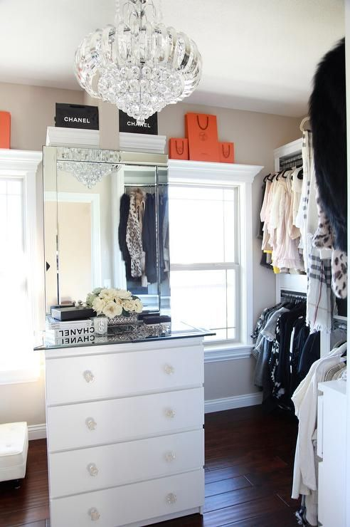 Beautiful walk in closet boasts a white built in dresser accented with glass knobs and a glass countertop topped with a frameless glass mirror flanked by windows finished with a window ledge holding stacked Hermes and Chanel bags framed by beige colored walls illuminated by a crystal chandelier while the room is finished with stacked clothes rails.