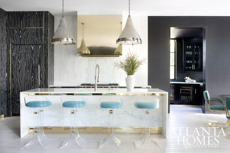 Black-and-white veneered cabinets continue the space's seamless movement, finished with a grouping of four vintage Lucite and brass stools.