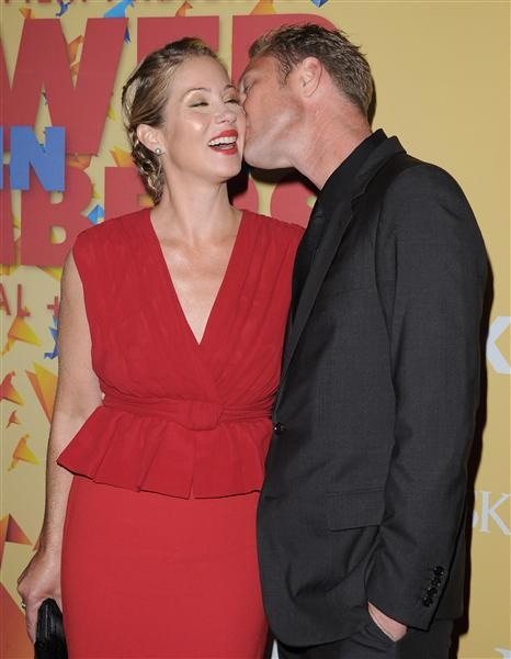 Look at that lover's glow! Christina Applegate looks happier than can be while fiancé Martyn Lenoble plants a big ol' wet one on his sweetheart's cheek.