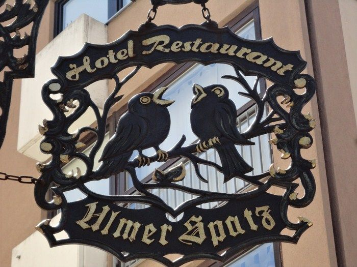 This is an unique artistic shop sign for a hotel and restaurant called 'Ulmer Spatz' (Sparrow of Ulm). It is located at the 'Münsterplatz' in Ulm, Germany, Baden-Württenberg.