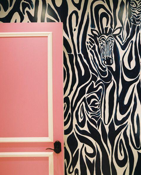 Zebra-print wallpaper layered behind a pink door