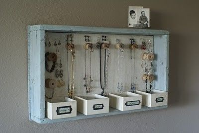 Hanging jewelry box. It looks like empty spools of thread for the hangars, something in the back to hang earrings on, and cute little boxes for all the extras.