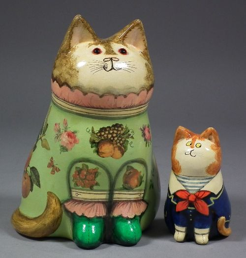 Joan & David De Bethel - A decorated papier-mache seated figure of a cat wearing a sailor suit (1976) and a ceramic cat wearing green fruit decorated dress (1996)