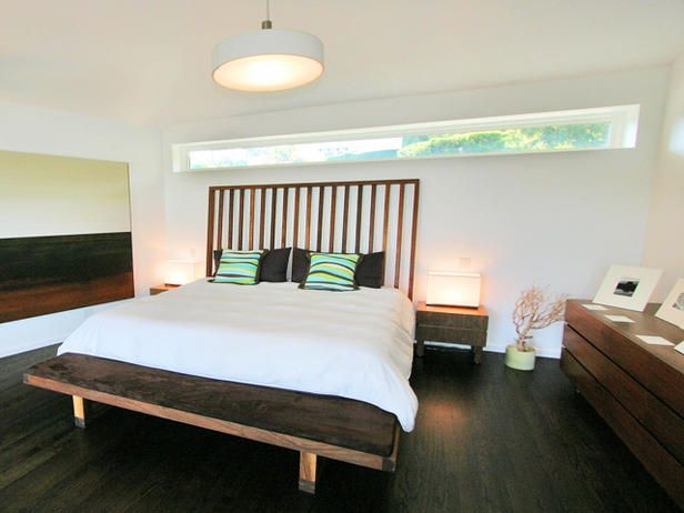 A custom wood bed with a slatted headboard and upholstered foot bench is the focal point of this modern bedroom remodel.