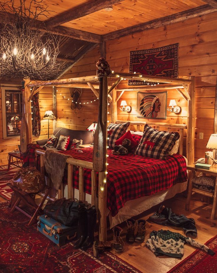 Cozy cabin de luxe! Swooning over this woodsy wonder bedroom space adorned in black and red buffalo check tucked away in a log canopy frame stringed with twinkling Christmas lights...The antler chandlier tops this bedroom off with ultimate rustic chic style!