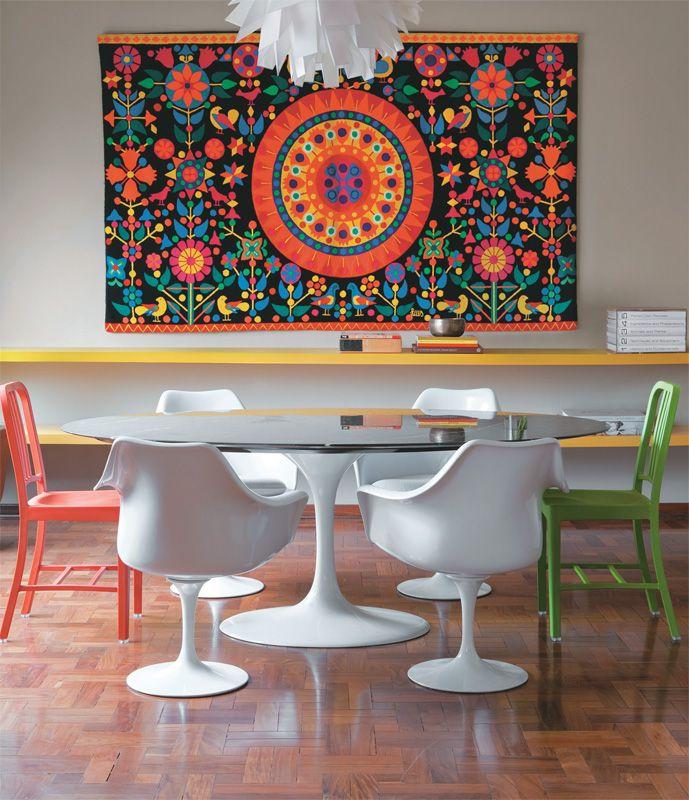 """O colorido traz alegria. Neste apartamento alugado, o arquiteto Gustavo Calazans montou a sala de jantar com móveis que o casal de moradores trouxe na mudança. """"A mesa e as cadeiras Tulipa são clássicas e fáceis de combinar. Sugeri mesclá-las a duas cadeiras coloridas, que estavam na cozinha"""", conta. A tapeçaria venezuelana, presente da mãe do proprietário, alegrou a parede, na qual pranchões laqueados (Fábrica de Móveis Araujo) compõem o aparador. Lustre da Scandinavia Designs."""