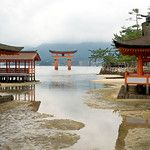 As the tide rolls in toward Itsukushima Shrine, water floods over the massive wooden legs of Torii Gate on Miyajima Island, just across the bay from Hiroshima, Japan