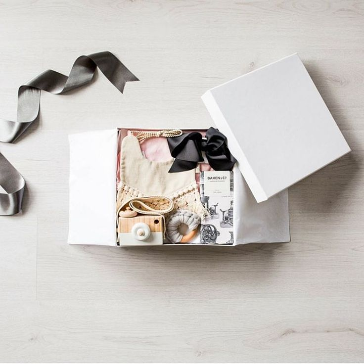Our baby hamper box 'Little Harmony' in a flatlay.    Box featuring romper, large bow headband,  wooden camera, chocolate, bib and a teether. #babygifts