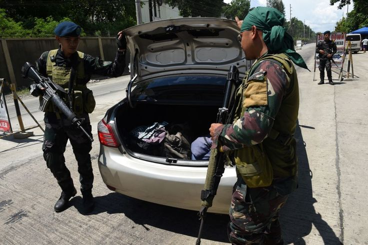"""Philippine policemen check a car boot of a resident fleeing from Marawi city, where gunmen who had declared allegiance to the Islamic State group rampaged through the southern city, at a checkpoint in Iligan City, in southern island of Mindanao on May 24, 2017. Philippine President Rodrigo Duterte warned that martial law would be """"harsh"""" and like a dictatorship, after imposing military rule in the south of the country to combat Islamist militants. / AFP PHOTO / TED ALJIBE (Photo credit…"""