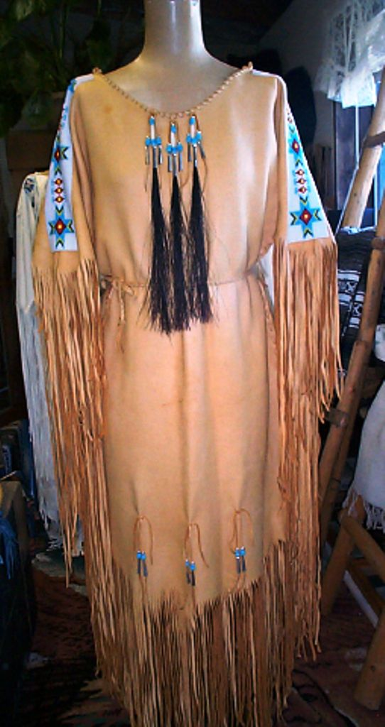 Gold deer hide dress that is all hand sewn and stitched with loom beadwork, horse hair tassels, bone hair pipe, glass beads, tin cones and lots of fringe. http://nativeamericanstuff.net/Native%20American%20Style%20Crafted%20Clothing%20buckskins%20outfits%20moccasins%20and%20Handbags.htm