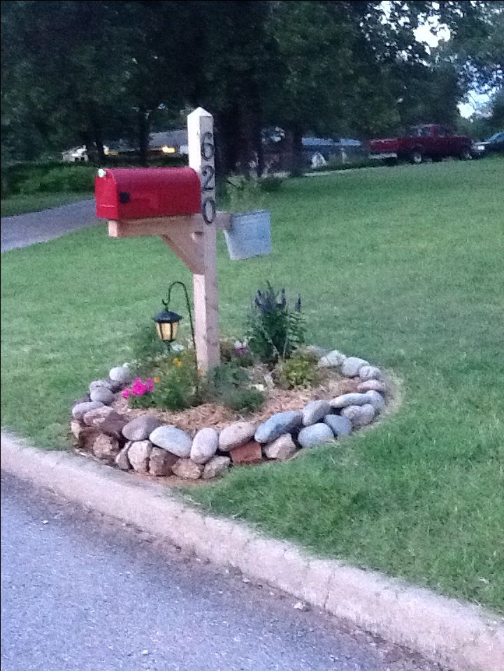 This is our mailbox makeover. I wanted a mailbox garden  I wanted it to match the style of our home. We went with a rock border, hung an old pail with flowers, and planted perennials to make it easy  not have to plant too many new plants next year. You can't see the knob but it is a white porcelain type knob with pretty flowers. And the final touch is the solar lantern. Because our house is very dark at night, I wanted to have the lantern to spot out house when we come home at night.