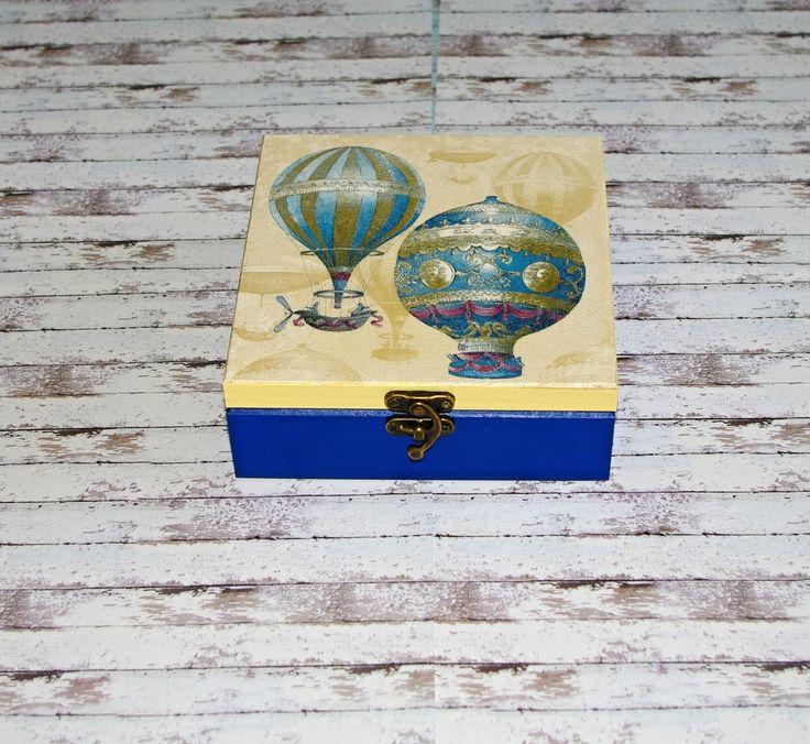 Vzducholod+s+balónem+Dřevěná+krabička+o+rozměrech+cca+16,2x16,2+cm+a+výšce6+cm.+Krabička+je+natřena+akrylovými+barvami,+ozdobená+technikou+decoupagea+zapínáním.+Následně+přetřena+lakem+s+atestem+na+hračky,+uvnitř+nechána+přírodní.