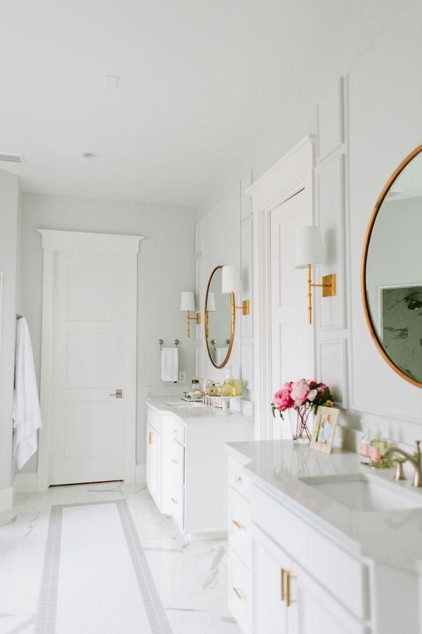 Stunning all-white master bathroom with gray and white carrara marble flooring, brass wall sconces with lamp shades, round vanity mirrors with gold frames, bright brass sink faucets, gray marble counter tops and classic traditional white cabinets.