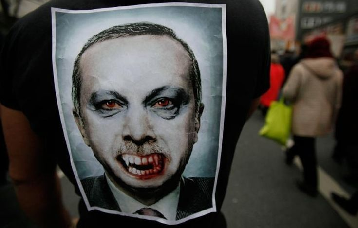 A protestor with a PM Erdogan paper mask.