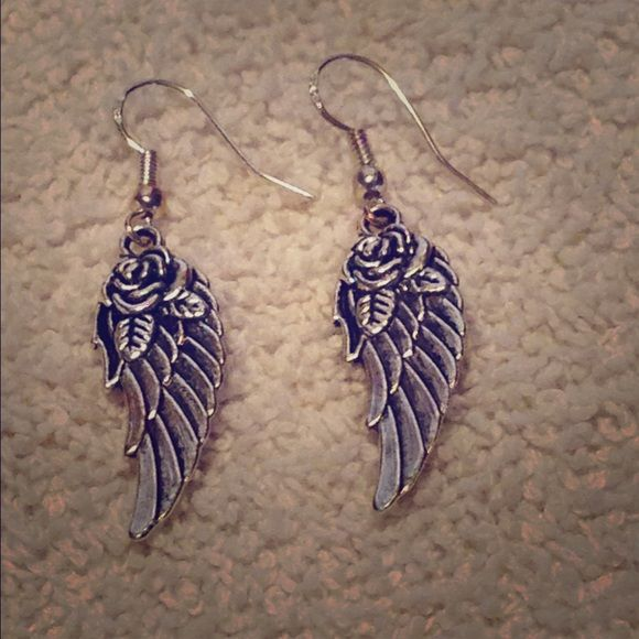 Lovely silver plated angel wings roses earrings Made from a stunning silver plated alloy, these lovely earrings add a nice shine to every outfit. Feathered angel wings adorned with roses are a great feminine symbol. These earrings are nickel-free. Jewelry Earrings
