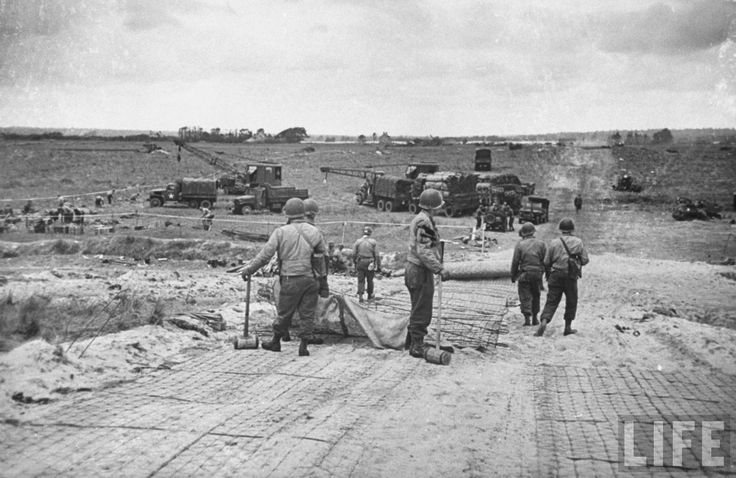 US Army engineers putting down wire mats on soft sand to create roads leading from beach. June 7, 1944. Photographer: Bob Landry