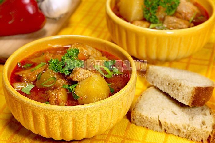 Венгерский суп-гуляш со свининой Продукты для приготовления супа-гуляша со свининой:  500 гр. свинины 7-8 картофелин 1 морковка 2 красных сладких перца Чеснок по вкусу 1 ч. л. семян тмина 4 луковицы 2 ст. л. молотой паприки Соль по вкусу 2 ст. л. томатного соуса Приготовление: Все овощи нарезать крупно, свинину кусочками примерно 3х3 см. В глубокой сковороде с толстым дном разогреть 4 ст. л. растительного масла. Лук на тихом огне тушить до мягкости и немного его подрумянить. Выложить к луку…