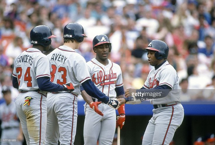 Terry Pendleton #9 of the Atlanta Braves Iis congratulated by Dion Sanders #24, Ron Gant #5 and Steve Avery #33 after Pendleton hit a three-run homer against the New York Mets during an Major League Baseball game circa 1992 at Shea Stadium in the Queens borough of New York City. Pendleton played for the Braves from 1991-94.