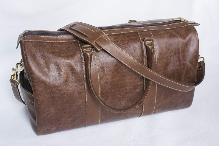This duffle or weekend bag is hand made with 100% real full and top grain leather. These are the two highest qualities of leather. This bag is perfect for a weekend getaway to the cottage, for your day of golf, tennis, or just spending time away from home. One of the beautiful things about having something made from natural materials is the aging process. As time goes by the leather will change, age, and build character.