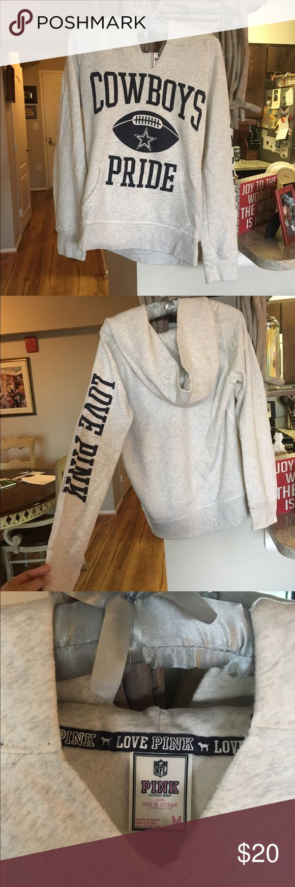 """Women's Dallas Cowboys Hoodie Entry worn, very comfortable hooded sweatshirt. Size medium, by PINK, Victoria's Secret with 5th & Ocean clothing line. One sleeve has """"LOVE PINK"""" written on it. Top to bottom approx 24.5"""". No stains, tears or rips. Very comfy! Color is a light heather creamy grey. Front double entry pocket. PINK Victoria's Secret Sweaters"""