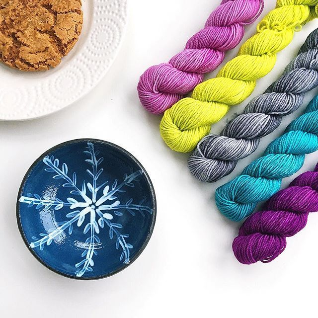 """From yesterday's snowy Sunday . Trying to choose a shawl pattern for the @greensnightout shawl project that could include these """" unicorn tail"""" skeins . Plus a little snowflake design bowl from the latest firing . Wishing you all a good week - what are your plans ? . . Plus  if you'd like the chance of a little snail mail from me  add a comment to my previous post and I'll pick a name at random later on . I received such a cheerful envelope from @ingthings that I thought it would be nice to…"""
