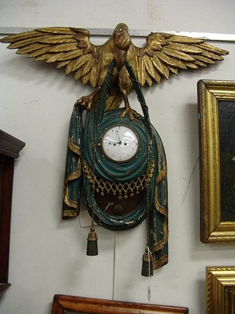 "Continental carved gilt eagle with suspended carved green painted drape and tassels holding an enamel clock face, 31"" x 30"". Provenance: sold at auction October 1978 by Sotheby Parke Bernet, Estate of Sally Fenelon-Young - Realized Price: $10,000.00"
