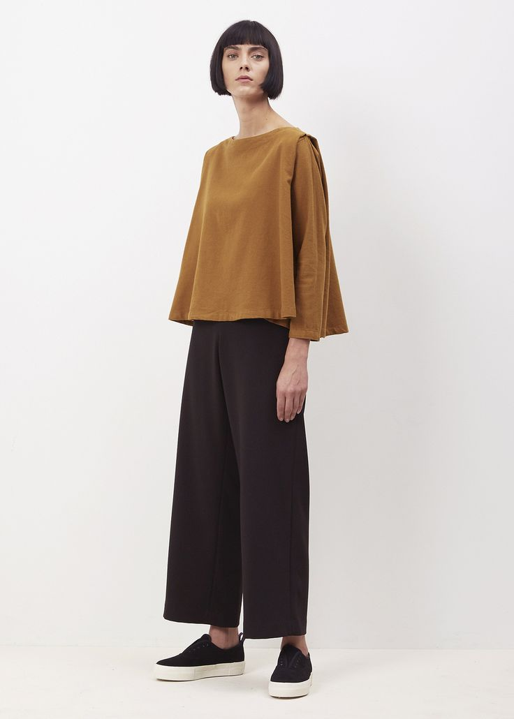 Long sleeve top with boat neck and wide, bell-shaped body. Pleated shoulder with raglan sleeve construction. Machine wash cold, dry flat.