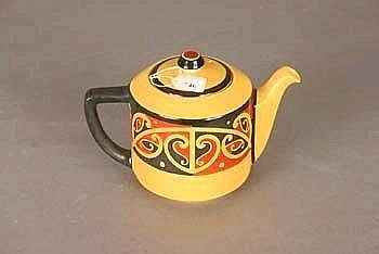 A Royal Doulton Maori Art Teapot c.1928, yellow ground; decorated with red and black kowhaiwhai patterned encircling band to the cylindrical...