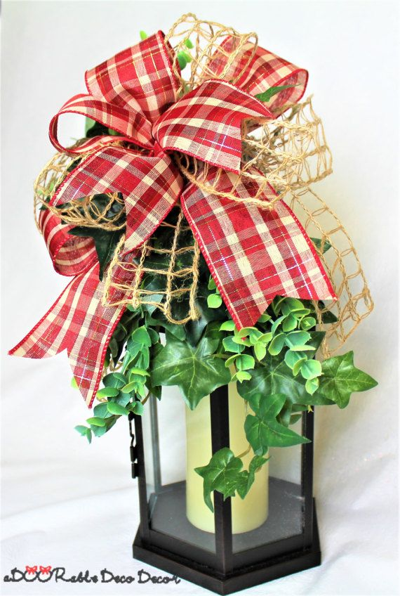 This Rustic Lantern Swag is a easy way to decorate your home in the farmhouse or primitive style. This swag can be used for every season of the year. It can be tied onto your own lantern and placed on top of a mantle, by the fireplace, placed on coffee or dining table top. It could also be tied on a banister post. It has lush greenery with ivy and eucalyptus that is secured with a large bow made with natural windowpane burlap ribbon and another red and ivory plaid ribbon . Approximate…