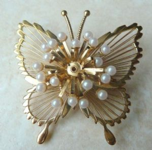 A vintage pearl detailed butterfly brooch by Monet.  The butterfly has beautiful wire work to its wings which are studded with faux pearl beads. The brooch is set in gold tone metal and is signed Monet with the copyright symbol to the back.  Circa 1980's.