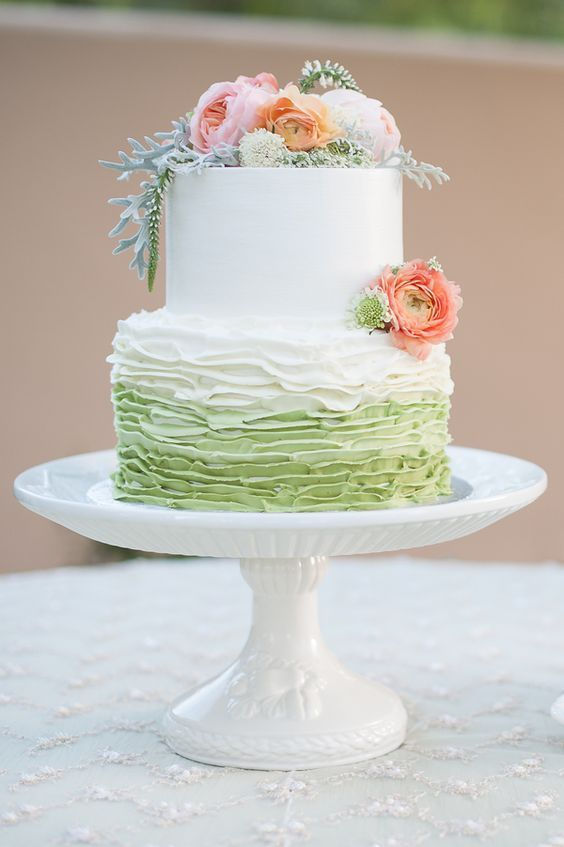 Beautiful white wedding cake with apple green base and flower topper.