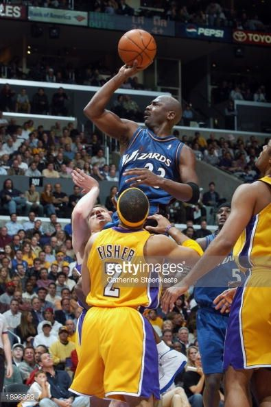 Michael Jordan of the Washington Wizards goes up for the shot against Mark Madsen and Derek Fisher of the Los Angeles Lakers during the NBA game at...