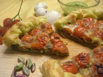La torta salata ai funghi, pomodorini e pesto è un piatto ideale in estate reso incredibilmente goloso dall'aggiunta dei pistacchi e del pesto di basilico.