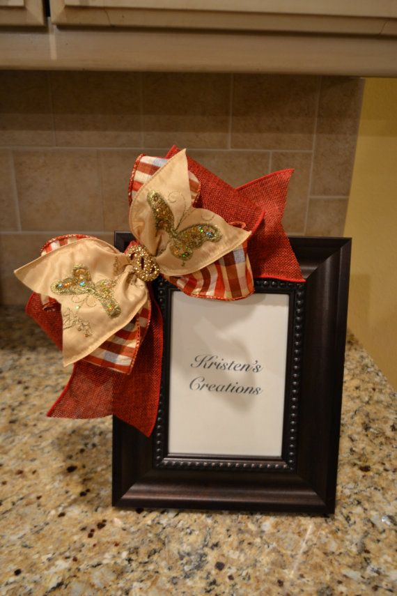 This frame is embellished with beautiful ribbons in red and gold. It would look good in any room of the house and would also make a great gift.