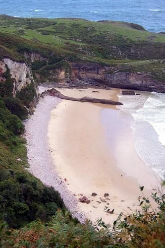 Playa de Ballota, Cué, LLanes, Asturias. Espectacular playa con zona para la práctica del nudismo; Fondo de arena y agua limpísima. Se puede ir en coche hasta muy cerca por camino de tierra bastante acondicionado. Características: Arena Blanca / Fuerte oleaje / Longitud:350 (m) / Anchura:62 (m)
