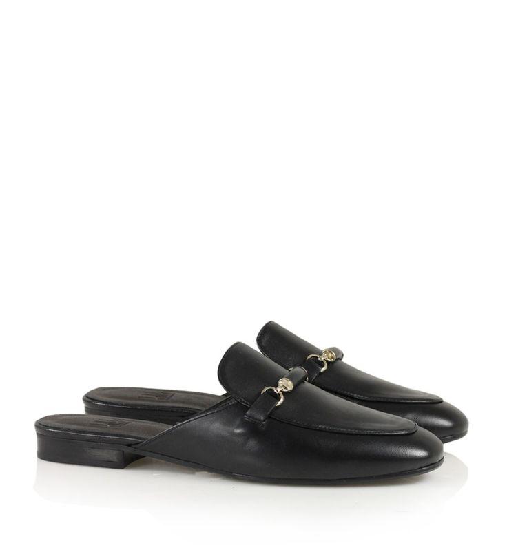 Sort loafer-inspireret slip-on i læder med firkantet tå og dekorativ guldkæde med læderdetalje fortil.
