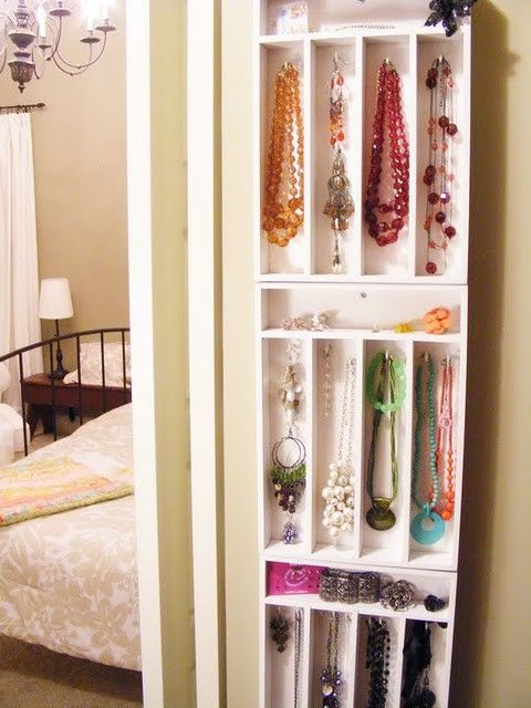 Cutlery trays stacked vertically on the wall hold jewelry. Perfect for next to the door inside a walk in closet! Especially if there's a large mirror hung nearby.