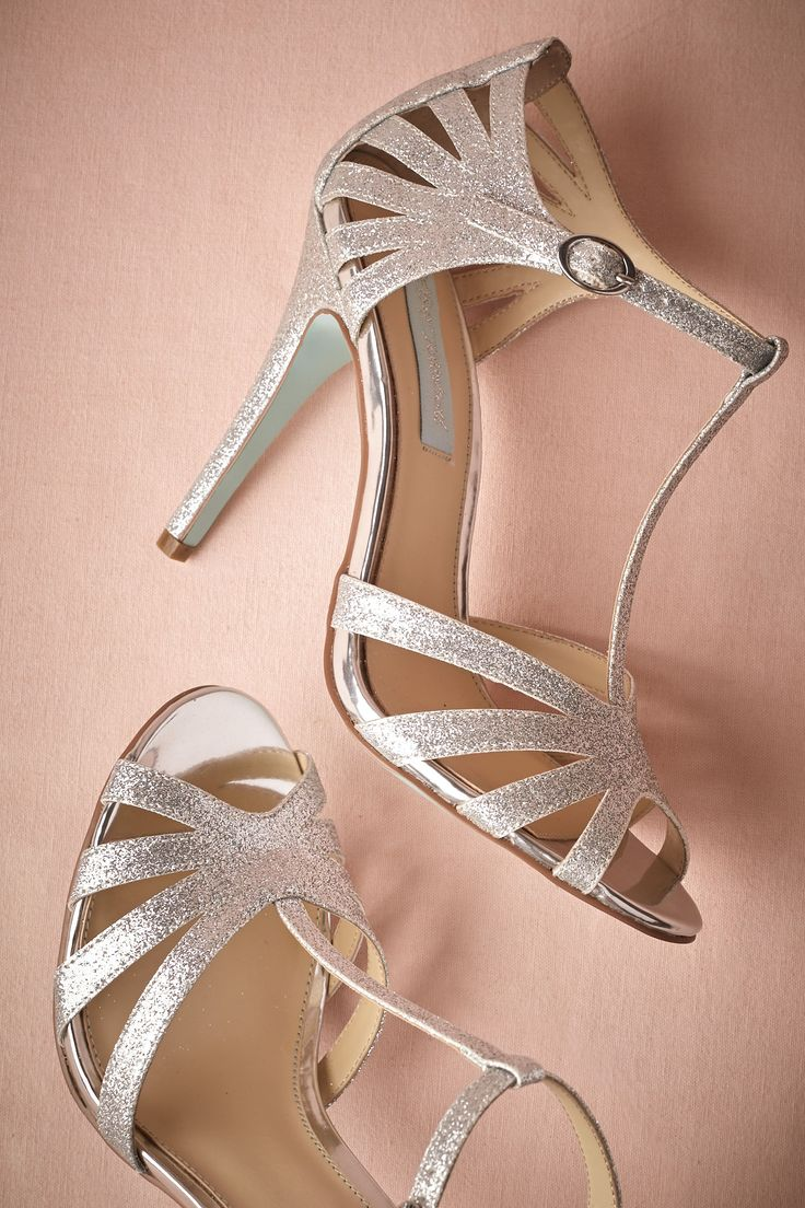 "BHLDN Stardust Heels |Betsey Johnson's lofty heels show off a light blue sole and glittery silver bands that swoop over and around into a vintage-inspired t-strap. Buckle closure. Glitter leather upper; leather insole. Synthetic sole. 4"" glitter leather wrapped heel."