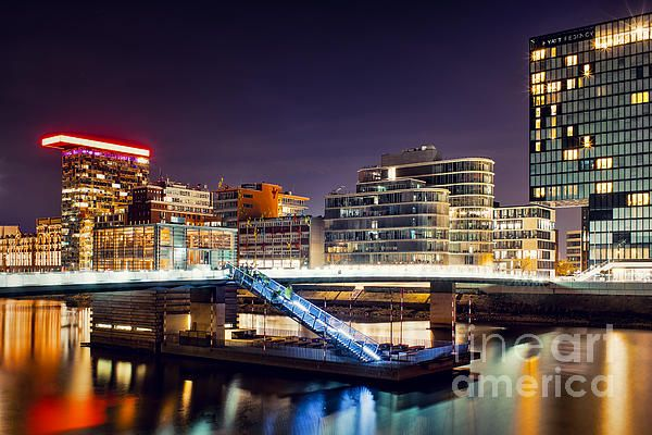 This picture shows a pedestrian bridge with a restaurant attracting people coming along. It's located in the Media Harbor in Dusseldorf, NRW, Germany.