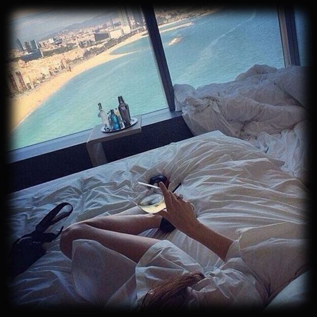 A glass of wine in bed overlooking the ocean…