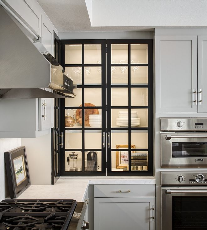 Black glass grid cabinet door The kitchen features a ...